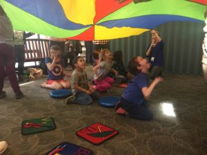 Children playing with the parachute at storytime.